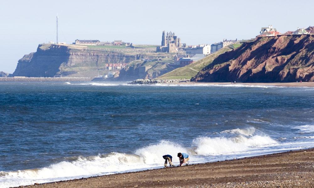 children on Whitby beach, Yorkshire, England