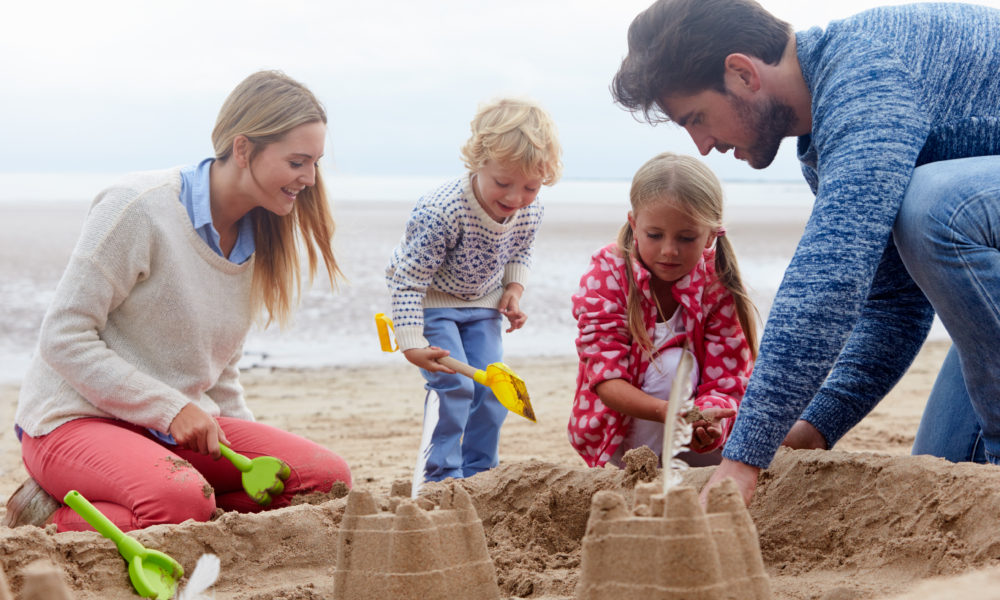 A family on the beach building sandcastles with their children.